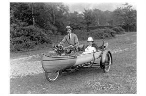Altes Foto Mann mit Motorrad und Frau in einem Kanu als Beiwagen (Neudruck als Postkarte)
