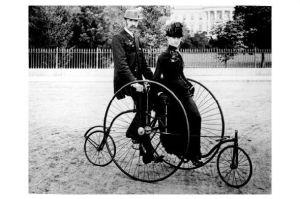 Altes Foto Mann und Frau auf Fahrrad stehend mit Stützrädern vorne und hinten (Neudruck als Postkarte)