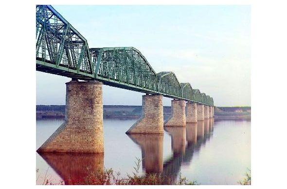 Altes Farbfoto Transsibirische Eisenbahn-Metallfachwerkbrücke auf Steinpfeilern über den Kama River in der Nähe von Perm im Ural (Neudruck als Postkarte)