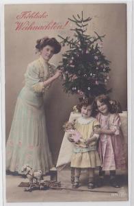 84293 Glückwunsch AK Fröhliche Weihnachten Dame mit Kindern neben Tannenbaum