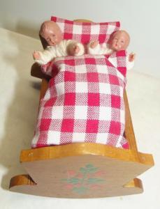 Zwei kleine Biege Puppen Püppchen in einer Wiege