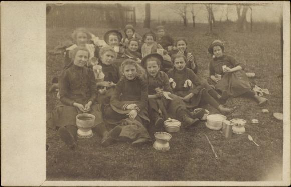 Foto Ak Mädchen auf einem Ausflug aufs Land, Gruppenfoto auf einer Wiese, Feldbesteck