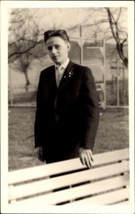 Foto Ak Portrait eines jungen Mannes in Anzug, Sitzbank