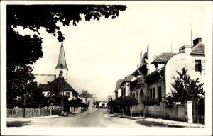 Ak Milovice nad Labem Milowitz Mittelböhmen, Straßenpartie im Ort, Häuser, Kirchturm