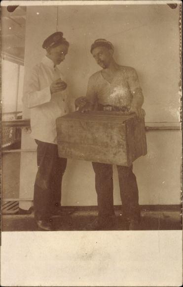 Foto Ak Zwei deutsche Matrosen mit einer Holzkiste Proviant, An Bord eines Dampfers