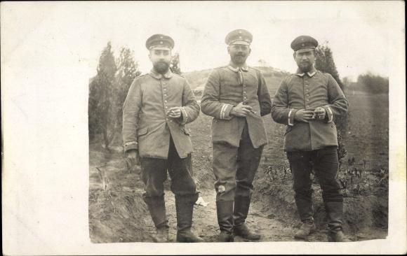 Foto Ak Drei deutsche Soldaten in Uniformen, Schirmmützen, Zigaretten rauchend, I. WK