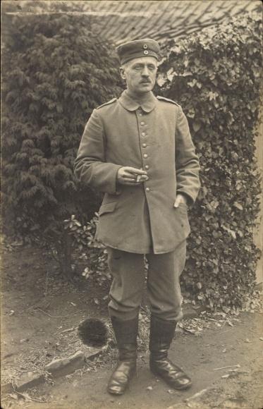 Foto Ak Deutscher Soldat in Uniform, Standportrait, Zigarre rauchend, Stiefel, I. WK