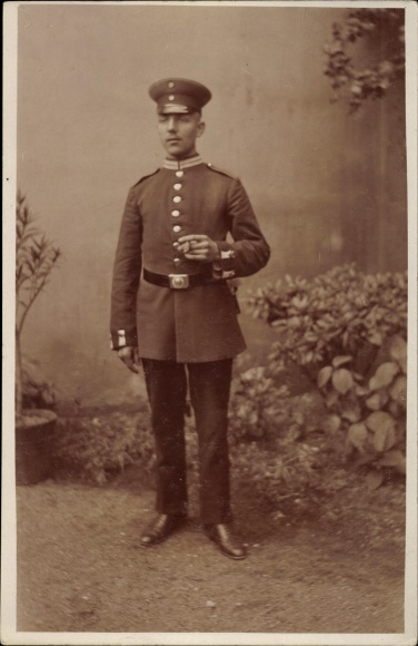 Foto Ak Deutscher Soldat in Uniform, Standportrait, Zigarre rauchend, Schirmmütze, I. WK