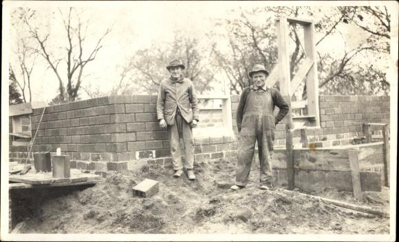 Foto Zwei Maurer vor dem Rohbau eines Hauses, Verlegen von Lochziegeln