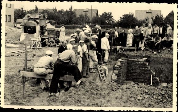Foto Maurer an den Grundmauern eines Hauses, Betonmischer, Zuschauer, Arbeiter