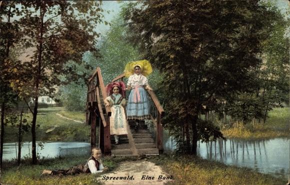 Ak Spreewald, Eine Bank, Frauen in Trachten auf einer Brücke, Junge im Gras