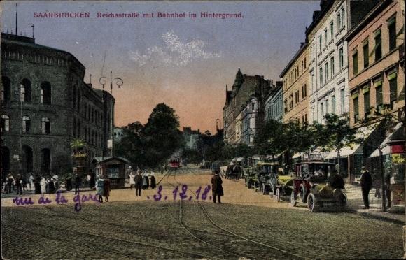 Ak Saarbrücken im Saarland, Reichsstraße mit Bahnhof im Hintergrund, Passanten
