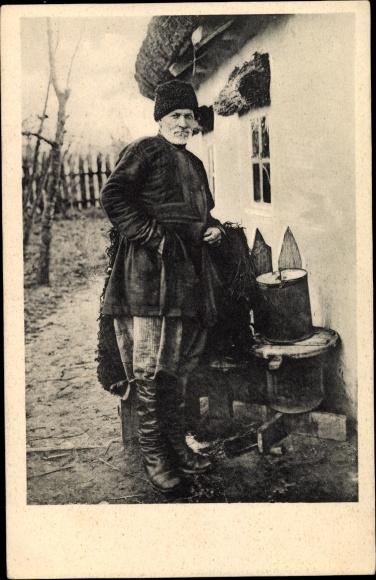 Ak Russland, Russischer Bauer vor einem Gartenzaun, Winterkleidung, Stiefel, Fellmütze