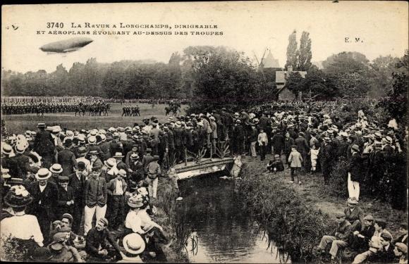 Ak La Revue à Longchamps, Dirigéable et Aéroplane évoluant au dessus des troupes