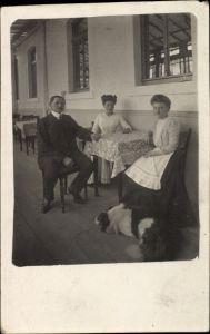 Foto Ak Pelzmühle?, Zwei Frauen und Mann an einem Tisch sitzend, Hund