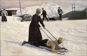 Ak Sport d'hiver, Wintersport, Zweier Schlitten, Frau stehend mit Griffen, Mann liegend
