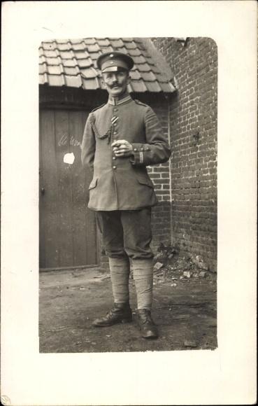 Foto Ak Deutscher Soldat in Uniform, Standportrait, Schirmmütze, Achselschnur, Zigarre, I. WK