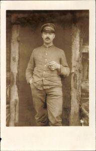 Foto Ak Soldat in Uniform mit Zigarre in der Hand vor einer Holzhütte, I. WK