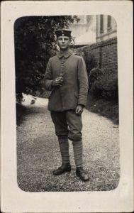 Foto Ak Junger Soldat in Uniform, Standportrait mit Zigarre, I. WK
