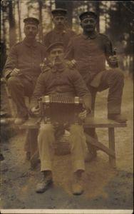 Foto Ak Vier Soldaten in Uniform in der Freizeit mit Ziehharmonika, Pfeife rauchend