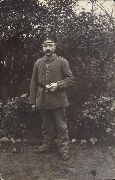 Foto Ak Deutscher Soldat in Uniform, Standportrait in einem Garten, Zigarre rauchend
