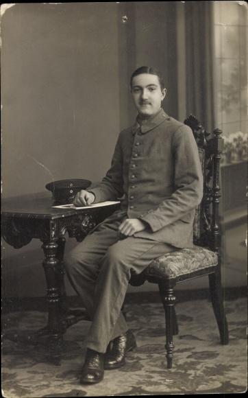 Foto Ak Soldat in Uniform, Sitzportrait an einem Tisch, Mütze