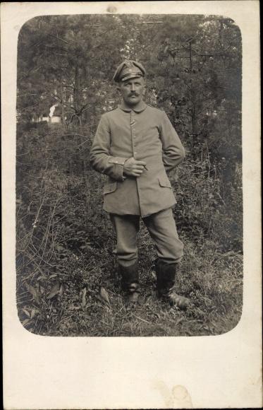 Foto Ak Deutscher Soldat in Uniform, Standportrait, Stiefel, Schirmmütze, Zigarre, I. WK