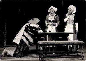 Ak Theaterszene, zwei Frauen, ein Mann kniet an einem Tisch