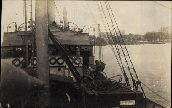 Foto Ak Matrosen an Bord eines Schiffes, Leuchtturm im Hintergrund, Partie an Deck