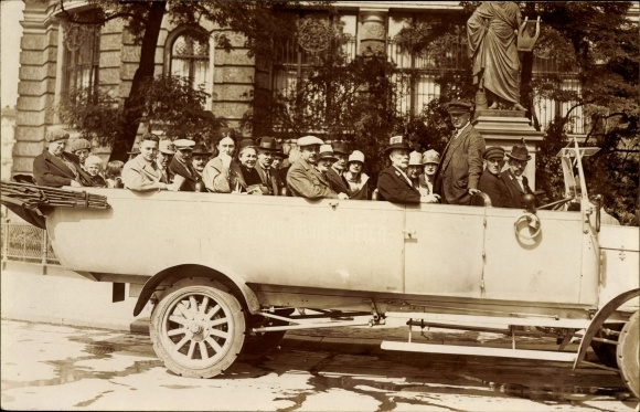 Foto Ak Passagiere in einem Rundfahrtenbus vor einem Denkmal
