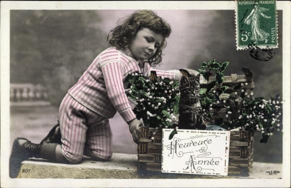 Ak Heureuse Année, Glückwunsch Neujahr, Mädchen mit junger Katze in einem Korb, Mistelzweige