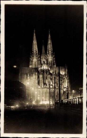 Foto Ak Köln am Rhein, Straßenpartie mit Blick auf den Dom bei Nacht