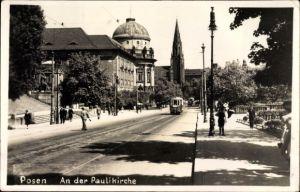 Foto Ak Poznań Posen, Straßenpartie an der Paulikirche, Passanten, Straßenbahn