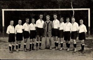 Foto Ak Fußballmannschaft in Trikots, Gruppenportrait vor dem Tor