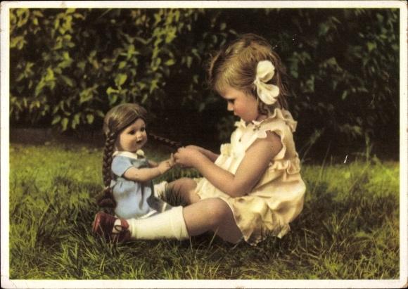 Ak Blondes Mädchen mit einer Puppe auf einer Wiese sitzend