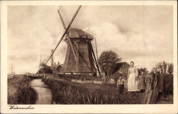 Ak Niederlande, Watermolen, Familie am Bachufer vor einer Windmühle