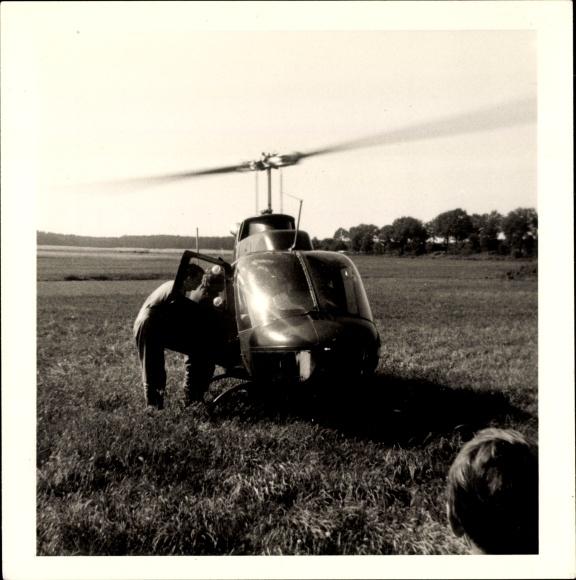 Foto Hubschrauber auf einem Feld, Gespräch der Piloten vor dem Start