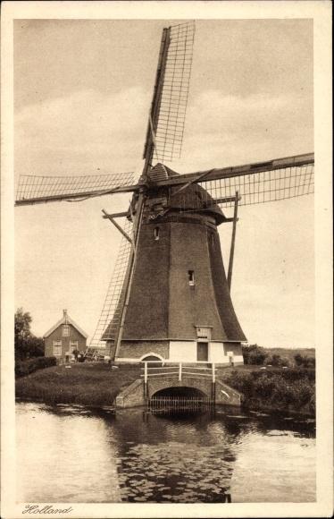 Ak Niederlande, Holland, Blick auf eine Windmühle am Wasser