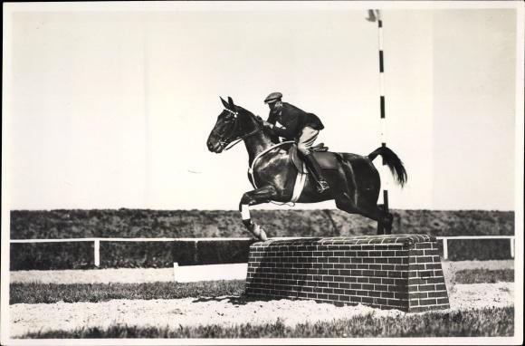 Foto Springreiter auf seinem Pferd, Sprung über ein Hindernis