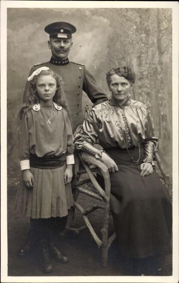 Foto Ak Soldat in Uniform mit Familie, Frau, Tochter, Schirmmütze mit Abzeichen, Kragenspiegel
