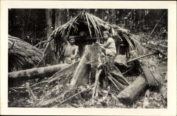 Foto Ak Brasilien, Brasilianische Indios an einem Baumstumpf