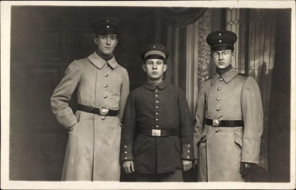 Foto Ak Drei deutsche Soldaten in Uniformen, Portrait, Schirmmützen, Mäntel, Gürtelschnallen