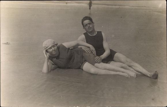 Foto Ak Mann und Frau in Badeanzügen am Strand im Wasser liegend, Badehaube