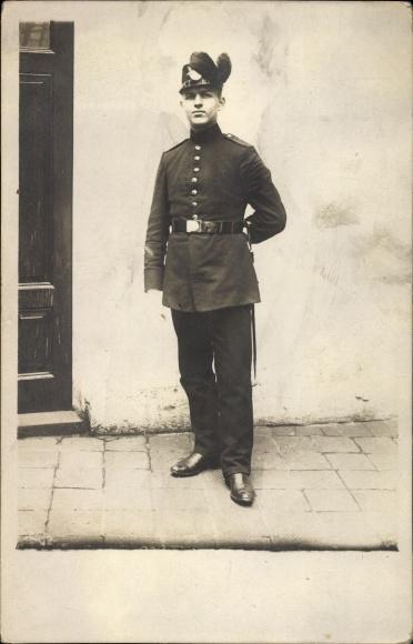 Foto Ak Deutscher Soldat in Uniform vor einer Haustür, Mütze mit Federschmuck