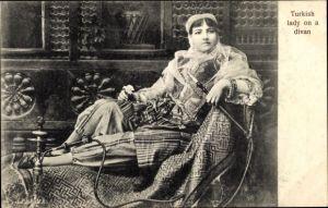 Ak Turkish on a divan, Nargile, Türkin in traditioneller Kleidung, Schischa, Wasserpfeife