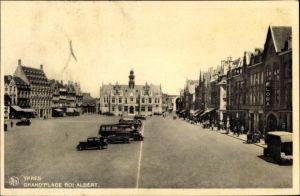 Ak Ypres Westflandern, Grand Place Roi Albert, Geschäftshäuser, Flora, Autos, Autobus