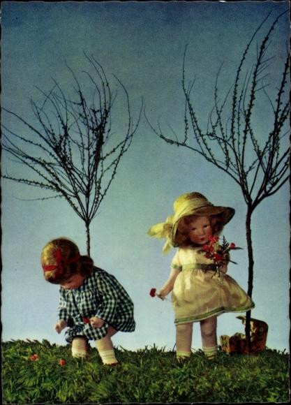 Ak Zwei Puppen auf einer Wiese, kahle Bäume, Käthe Kruse