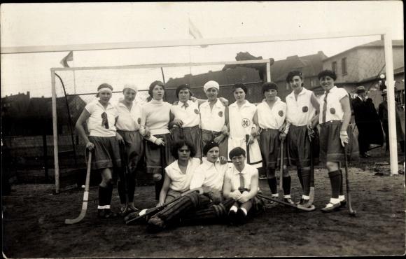 Foto Ak Mädchen Hockeymannschaft, Gruppenportrait vor einem Tor, Hockeyschläger