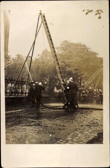 Foto Ak Feuerwehr bei einer Übung, Feuerwehrleiter, Löschschlauch