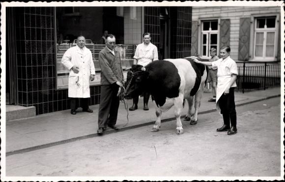 Foto Ak Schlachter, Gruppenportrait mit einem Rind vor einer Metzgerei